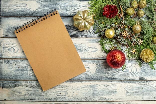 Bovenaanzicht een notebook xmas ornamenten fir boomtakken op houten achtergrond