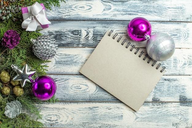 Bovenaanzicht een notitieblok klein cadeau fir tree takken xmas speelgoed op houten achtergrond
