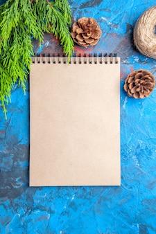 Bovenaanzicht een notitieboekje dennenboomtak en kegels op blauw-rode achtergrond