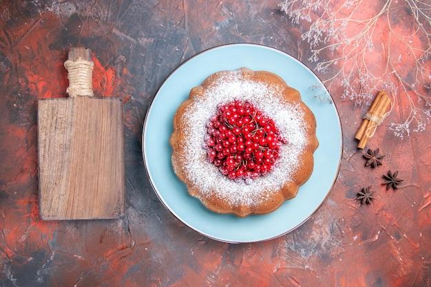Bovenaanzicht een smakelijke taart een taart de houten snijplank kaneelstokjes steranijs