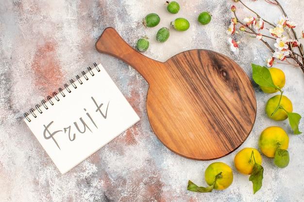 Bovenaanzicht een snijplank mandarijnen feykhoas fruit geschreven op notebook op naakte achtergrond