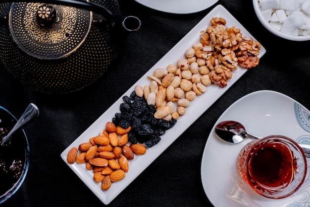 Bovenaanzicht een soort noten met rozijnen en een kopje thee