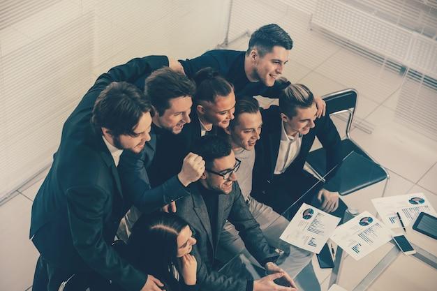 Bovenaanzicht. een succesvol business team zit aan een bureau en kijkt naar de camera.