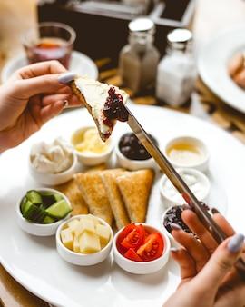 Bovenaanzicht een vrouw heeft ontbijt gebakken toast met honing boter zure room jam en olijven op een bord