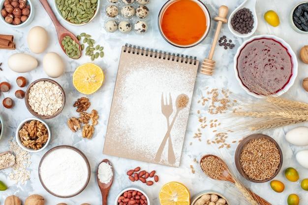 Bovenaanzicht eenvoudig notitieblok met eieren meel gelei en verschillende noten op witte noten suiker kleur taart foto deeg fruit zoete cake