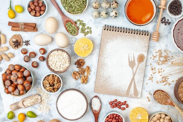 Bovenaanzicht eenvoudige notitieblok met eieren meel gelei en verschillende noten op witte noten suiker kleur taart deeg fruit zoete cake
