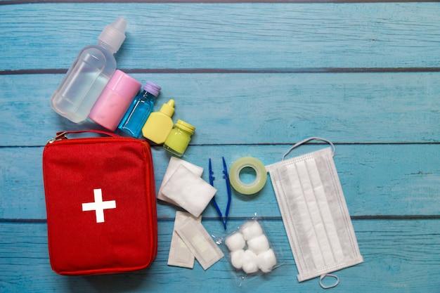 Bovenaanzicht eerste hulp tas kind met medische benodigdheden op hout achtergrond.