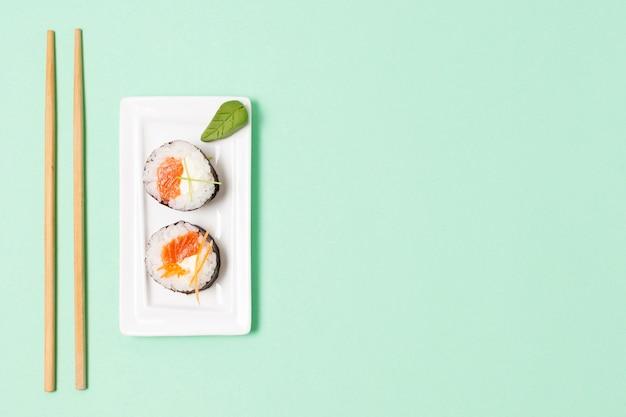 Bovenaanzicht eetstokjes naast plaat met sushi