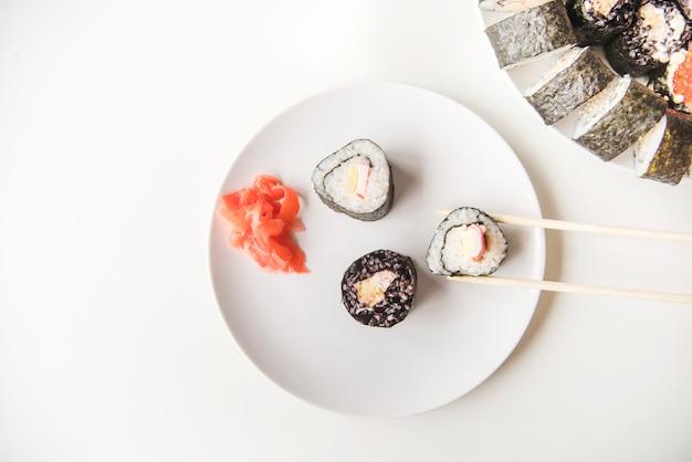 Bovenaanzicht eetstokjes op sushi plaat