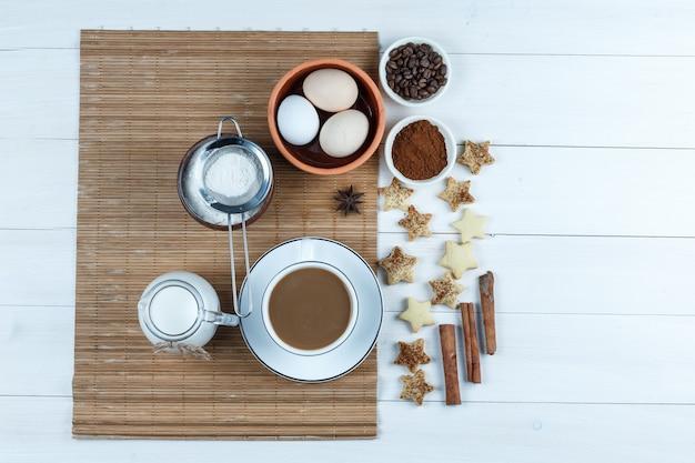 Bovenaanzicht eieren, kruik melk, kopje koffie, bloem op placemat met koffiebonen en bloem, ster cookies, kaneel op witte houten plank achtergrond. horizontaal