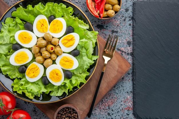Bovenaanzicht eiersalade groene salade en olijven op lichte achtergrond
