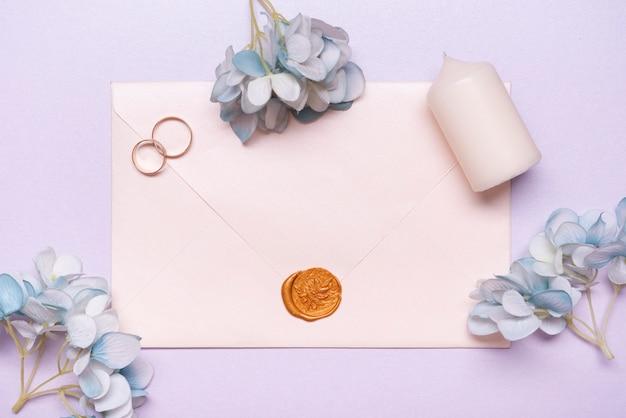 Bovenaanzicht elegante envelop met trouwringen