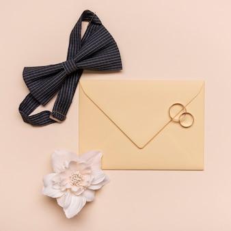 Bovenaanzicht elegante verlovingsringen met envelop en vlinderdas