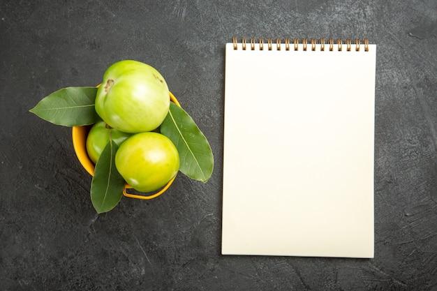 Bovenaanzicht emmer groene tomaten en laurierblaadjes en een notitieboekje op donkere achtergrond