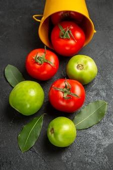 Bovenaanzicht emmer met rode en groene tomaten en laurierblaadjes op donkere achtergrond