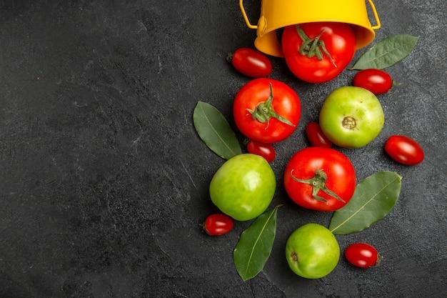 Bovenaanzicht emmer met rode groene en cherry tomaten laurierblaadjes op donkere grond met kopie ruimte