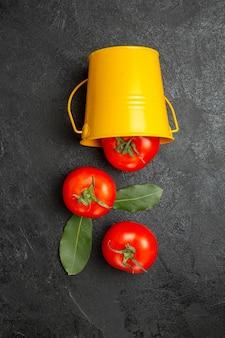 Bovenaanzicht emmer met rode tomaten op donkere achtergrond