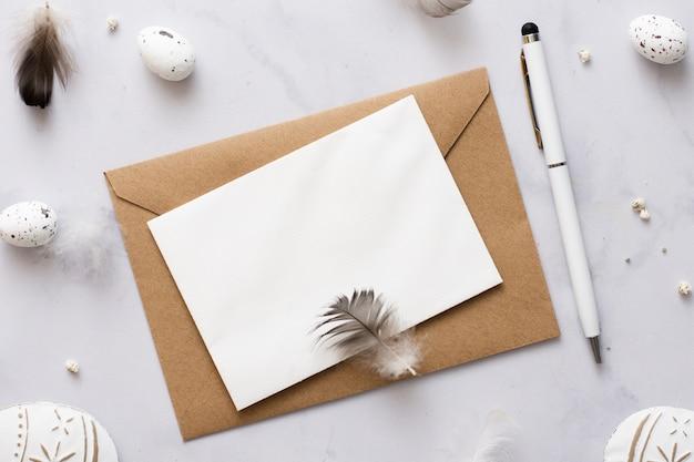 Bovenaanzicht envelop met pen omgeven door paaseieren