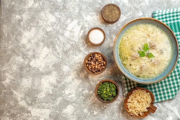 Bovenaanzicht erishte in kom verschillende levensmiddelen in kommen op grijze achtergrond