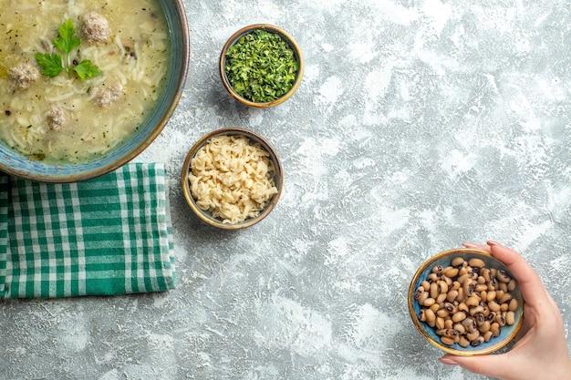 Bovenaanzicht erishte in kom verschillende voeders in kommen bean bol in vrouw hand op grijze achtergrond