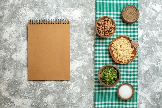Bovenaanzicht erishte in kom verschillende voeders in kommen kladblok op grijze achtergrond