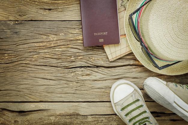 Bovenaanzicht essentiële items om te reizen. de kaart paspoort hoed en man schoen op rustieke houten achtergrond.