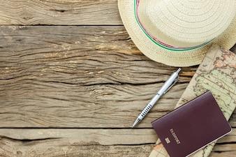 Bovenaanzicht essentiële punten om te reizen. De kaart paspoort hoed op rustieke houten achtergrond.