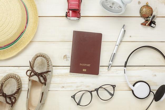 Bovenaanzicht essentiële reis items.the schoenen notitieboekje boom kaart paspoort vliegtuig auto bril op rustieke houten achtergrond.