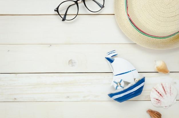 Bovenaanzicht essentiële reis zomer items.the boot bril hoed shell op witte houten achtergrond.