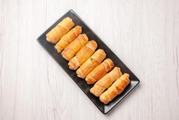Bovenaanzicht eten op de plaat buisvormig gebak op de donkere plaat op de witte tafel