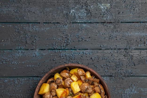 Bovenaanzicht eten op de tafelplaat met aardappelen en champignons onderaan de grijze tafel