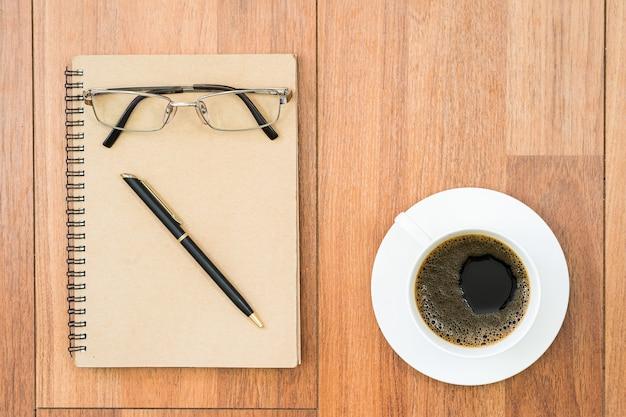Bovenaanzicht eyeglasse en pen op blocnote en koffiekopje op houten dek met kopie ruimte
