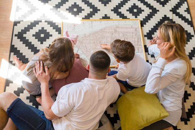 Bovenaanzicht familie binnenshuis kijken naar een blauwdruk
