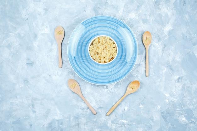 Bovenaanzicht farfalle pasta in kom en houten lepels met plaat op gips achtergrond. horizontaal