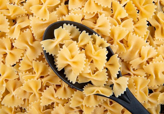 Bovenaanzicht farfalle pasta op zwarte lepel