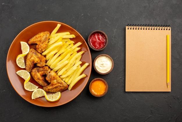 Bovenaanzicht fastfood bord met kippenvleugels, frietjes en citroen naast kommen met drie soorten sauzen en notitieboekje met potlood op tafel