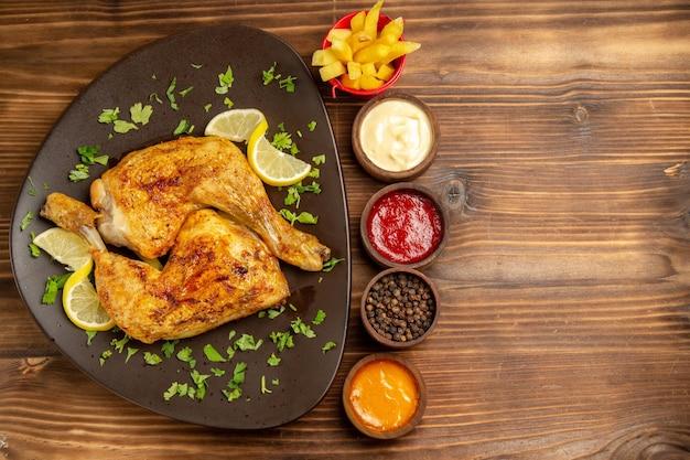 Bovenaanzicht fastfood in de plaat kip met citroen en kruiden in de plaat naast de kommen met zwarte pepersauzen en frietjes aan de linkerkant van de donkere tafel