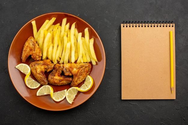 Bovenaanzicht fastfood oranje bord met frietjes, kippenvleugels en citroen naast het crèmekleurige notitieboekje en het gele potlood