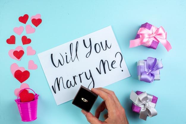 Bovenaanzicht februari concept rode en roze hartstickers verspreid uit mini-emmer wil je met me trouwen geschreven op papieren ring in mannenhand op blauwe tafel