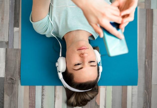 Bovenaanzicht fit vrouw, luisteren naar muziek