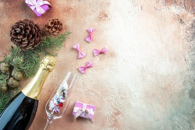 Bovenaanzicht fles champagne met kleine cadeautjes op licht xmas foto nieuwjaar kleur cadeau alcoholvrije ruimte