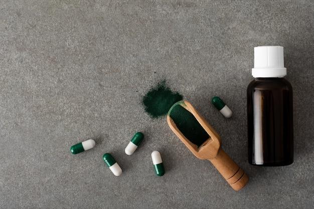 Bovenaanzicht fles olie met pillen op de tafel