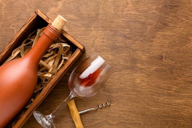 Bovenaanzicht fles wijn en glas met kurkentrekker en kopie-ruimte