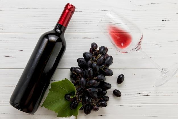 Bovenaanzicht fles wijn met glas en een tros druiven