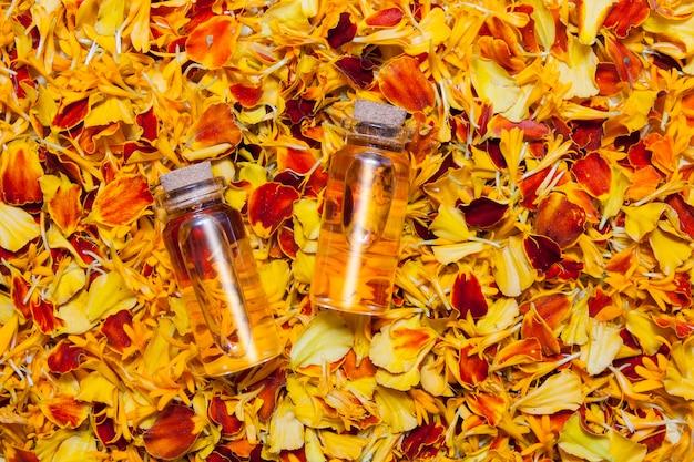 Bovenaanzicht flessen olie of tinctuur tegen een oppervlak van feloranje bloemblaadjes