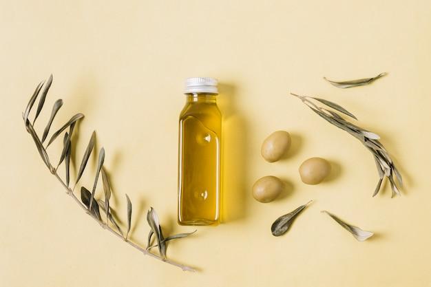 Bovenaanzicht flessen olijfolie met rozemarijn en olijven