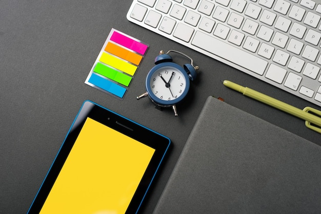 Bovenaanzicht foto van bureau met tablet toetsenbord planner agenda wekker
