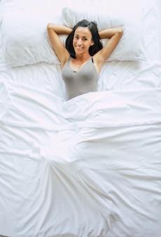 Bovenaanzicht foto van de prachtige gelukkig brunette vrouw in een groot wit bed in haar slaapkamer. ontspan thuis in het weekend
