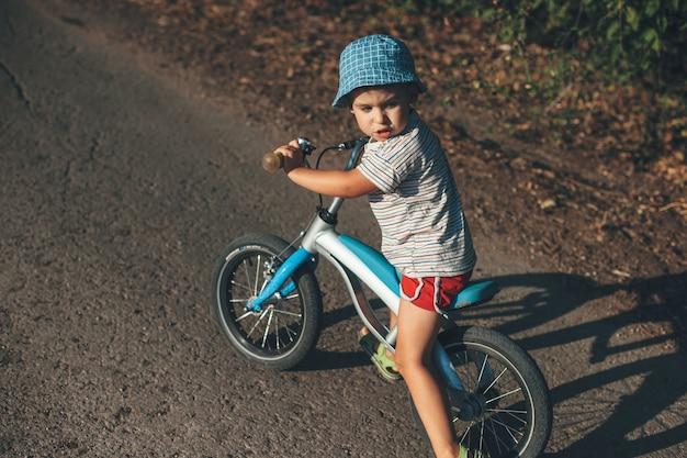 Bovenaanzicht foto van een blanke jongen die terugkijkt tijdens het fietsen op een landweg