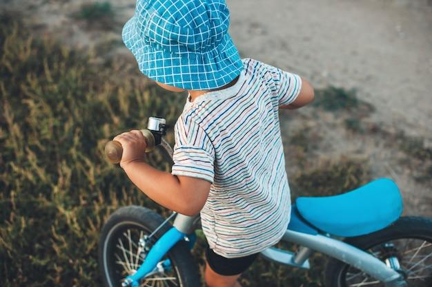 Bovenaanzicht foto van een blanke jongen met blauwe hoed rijden op een fiets in het veld